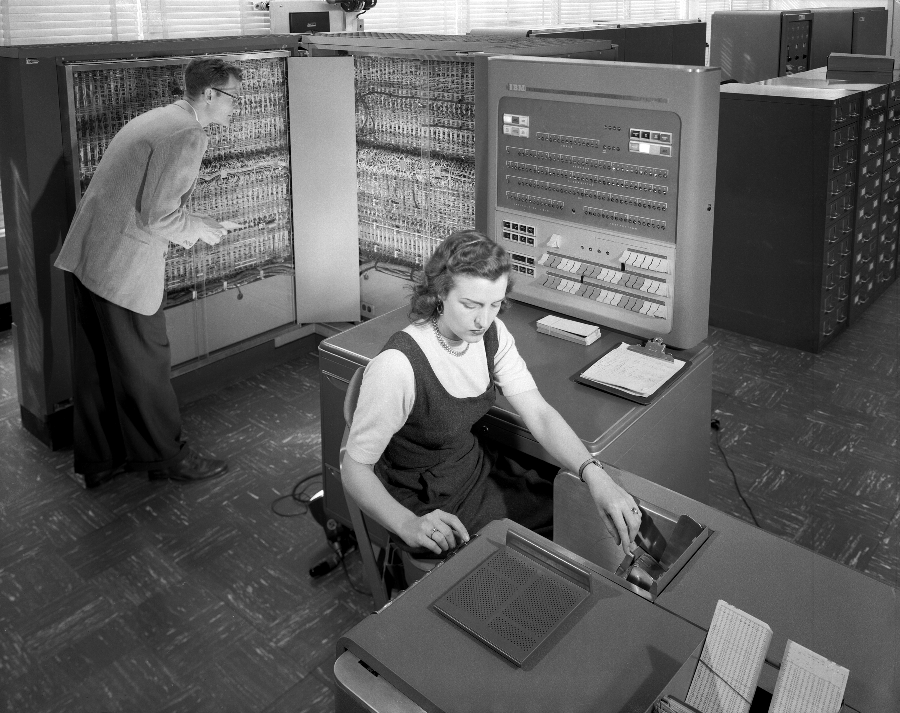 An old picture of a young man and woman shown working on an IBM 704 data machine.