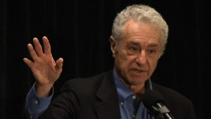Headshot photo of Gar Alperovitz speaking, He is speaking into a mic and gesturing with his right hand.
